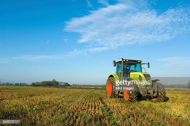 a tractor in a stubble field in gloucestershire. - tractor stock pictures, royalty-free photos & images