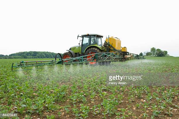 tractor in field spraying crop - crop sprayer stock pictures, royalty-free photos & images