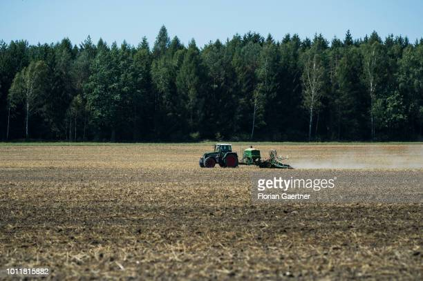 A tractor is pictured during working on a harvested field on August 01 2018 in Diehsa Germany Farmers complain harvest losses because of the dry...
