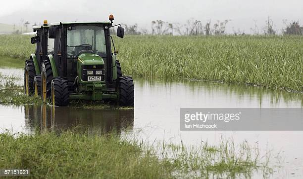 A tractor lies stranded in a flooded sugarcane plantation March 22 2006 in Innisfail Australia Tropical Cyclone Larry crossed the coast as a category...