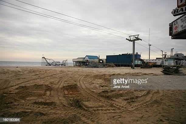 CONTENT] Tractor marks in the sand where the Seaside Heights boardwalk once stood post Hurricane Sandy with view of the Jet Star roller coaster the...