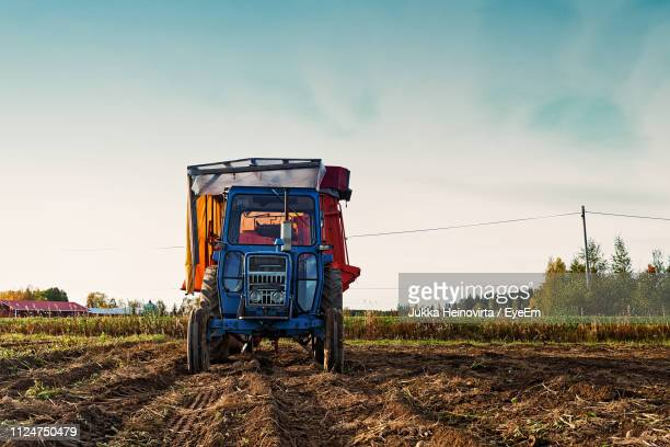 tractor on agricultural field against sky - heinovirta stock photos and pictures