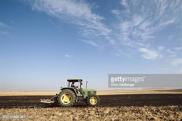 tractor on barren wheat field, autumn, side view - トラクター ストックフォトと画像
