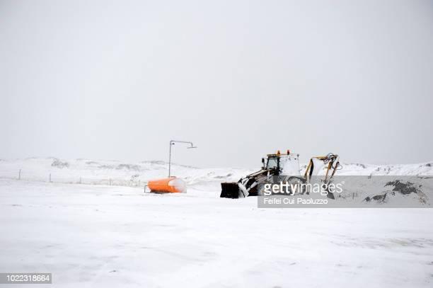 a tractor on the roadside near stykkishólmur, west iceland - schneefahrzeug stock-fotos und bilder