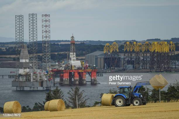 Tractor picks up hay bales in view of oil rigs and drilling platforms on September 8, 2020 in Cromarty, Scotland. Complaints from locals have spiked...