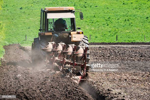 Tractor ploughing a field on a sunny spring day.