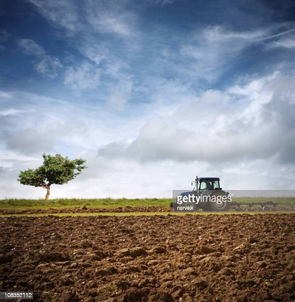 tractor ploughing on the field - tractor stock pictures, royalty-free photos & images