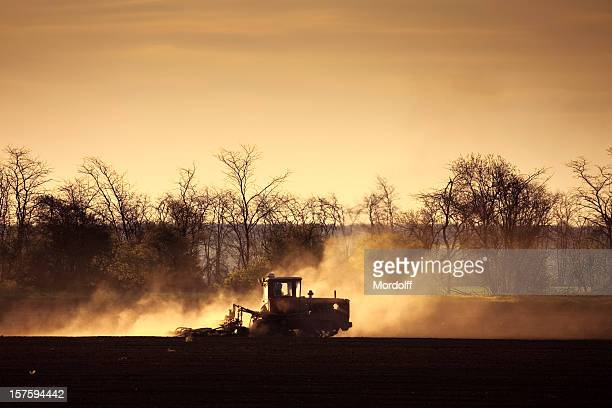 Tractor plowing field at sunset