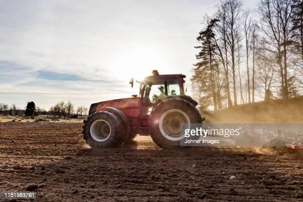 tractor plowing field - tractor stockfoto's en -beelden
