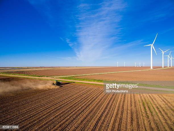 Tractor plowing field with wind turbinel farm in the distance