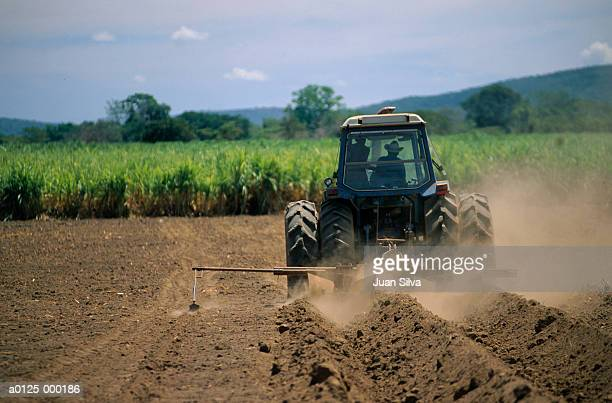 tractor plowing soil - agriculture stock pictures, royalty-free photos & images
