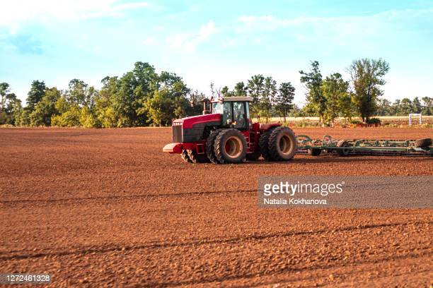 tractor plows land after harvesting preparing