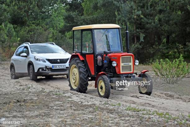 Tractor pulling a modern crossover through the sandy road