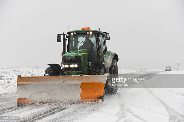 A tractor snow plough tries to keep the road open as heavy snow falls on the North Yorkshire Moors on January 26 2014 near Castleton England Strong...