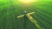 Tractor spray fertilizer on green field.