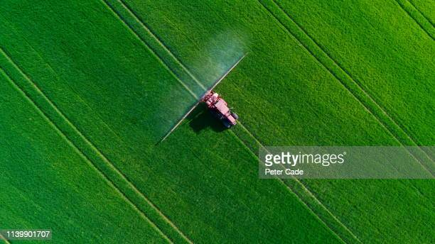 tractor spraying field - crop sprayer stock pictures, royalty-free photos & images