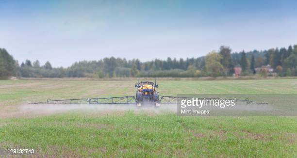tractor spraying herbicide - insecticide stock pictures, royalty-free photos & images