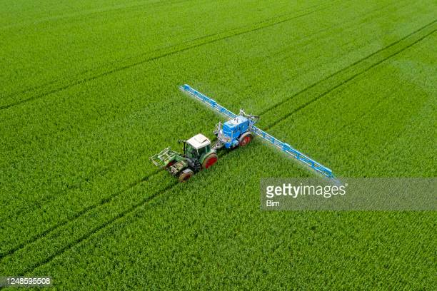 tractor spraying wheat field, aerial view - glyphosate stock pictures, royalty-free photos & images