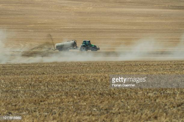 A tractor spreads manure on a harvested field on August 01 2018 in Koenigshain Germany Farmers complain harvest losses because of the dry weather...