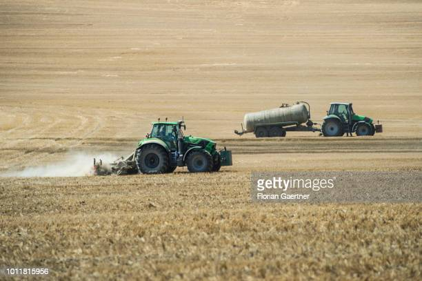 A tractor spreads manure while another tractor works on a harvested field on August 01 2018 in Koenigshain Germany Farmers complain harvest losses...