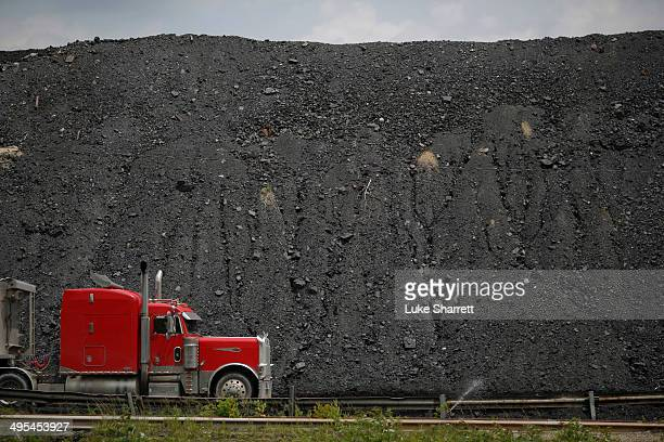 A tractor trailer drives by a mound of coal after delivering a truckload of coal to Arch Coal Terminals June 3 2014 in Cattletsburg Kentucky New...