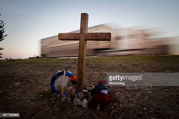 A tractor trailer drives past by a memorial to the victims of the North Central Texas College softball team at the crash site along I35 near Davis...