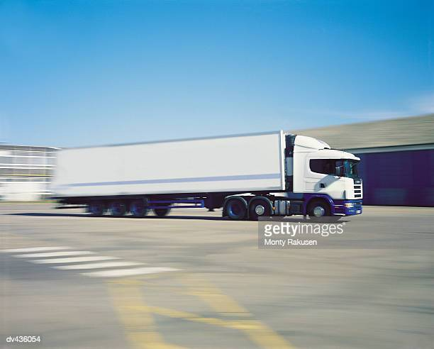 Tractor trailer driving through empty lot