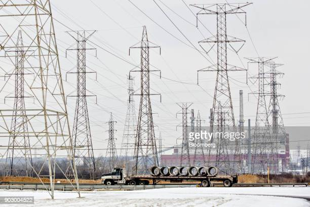 A tractor trailer truck passes in front of transmission towers near the NRG Energy Inc Will County Generating Station a coalfired power plant in...