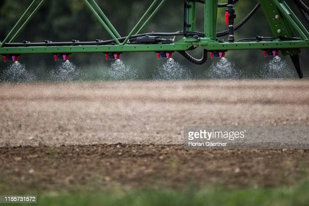 A tractor with a field sprayer is pictured on June 28 2019 in Koellitsch Germany