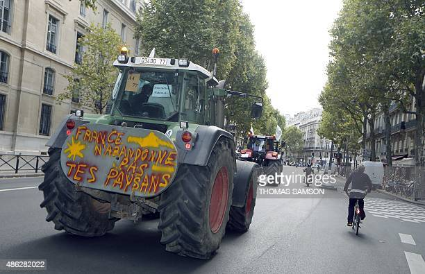 A tractor with a sign that reads 'France do not abandon your farmers' is driven along a street in Paris as farmers make their way to the French...