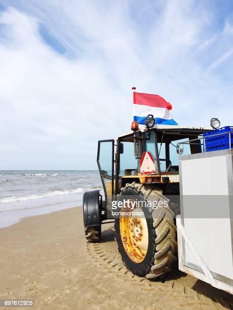 tractor with dutch flag at beach against sky - bortes stockfoto's en -beelden