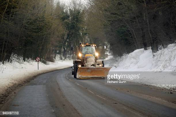 tractor with snowplough/snowplow fitted helping clear roads in rutland, england - march month stock pictures, royalty-free photos & images