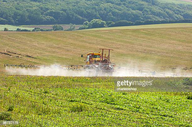 tractor with spray rig spraying fertilizer onto field - insecticide stock pictures, royalty-free photos & images