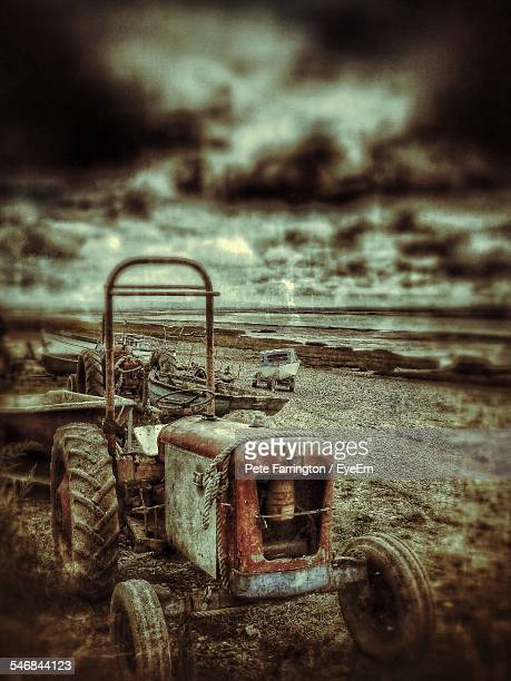 Tractors And Boats On Beach Against Cloudy Sky
