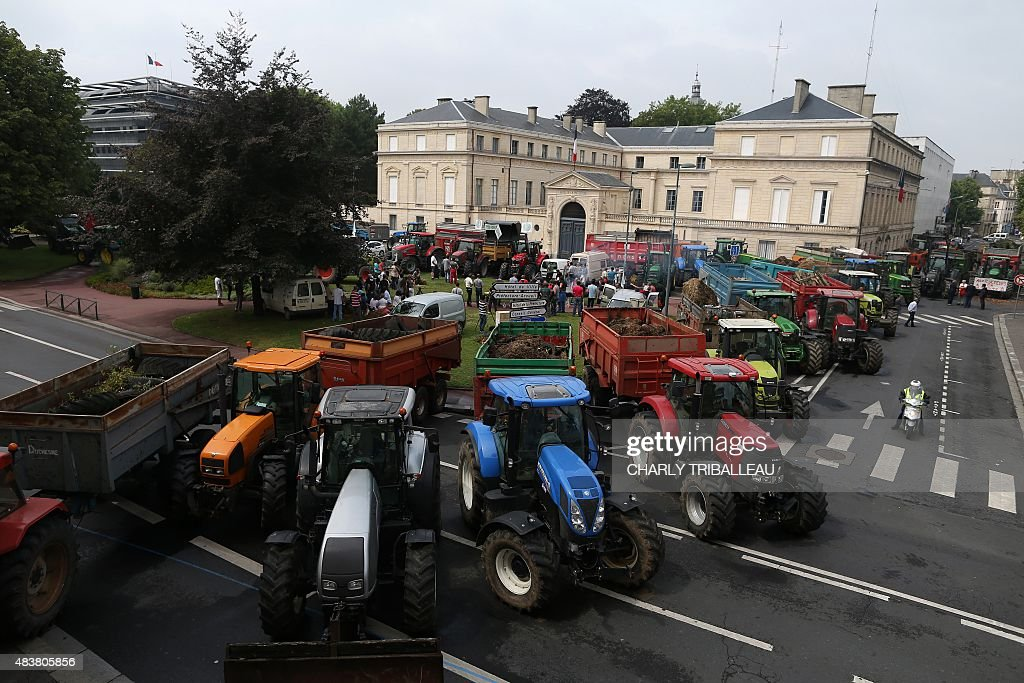 Tractors and farming trailers filled with trash are parked during a farmers' demonstration outside the Calvados prefecture in Caen, northwestern France, on August 13, 2015. Some 100 farmers demonstrated in Caen threatening to dump trash, according to police, ahead of a technical meeting at the prefecture in which the farmers requested the presence of dairy, slaughterhouse and food suppliers' representatives.