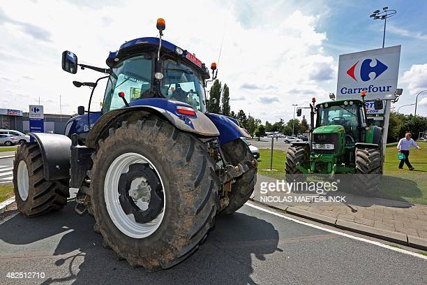 Tractors block access outside the Carrefour supermarket in Waterloo as part of a farmers' protest action on July 31 over falling food prices AFP...