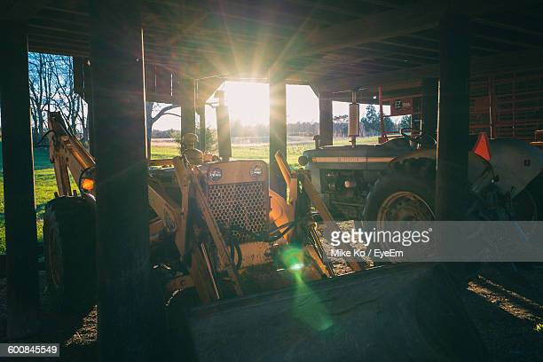 Tractors In Shed During Sunset