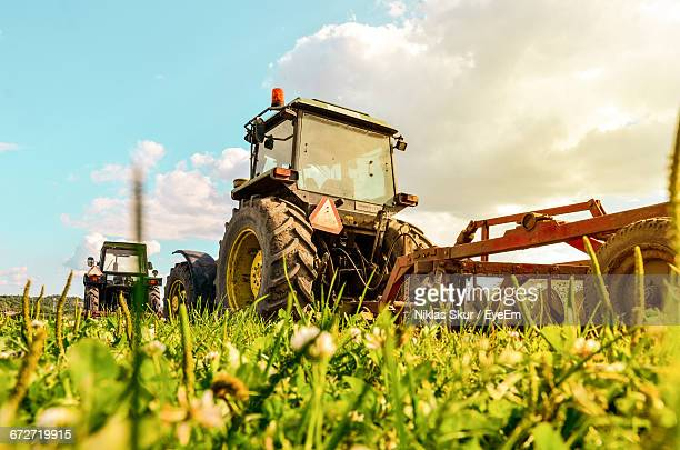 Tractors On Agricultural Field Against Sky