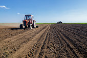 Tractors sowing on agricultural field in spring