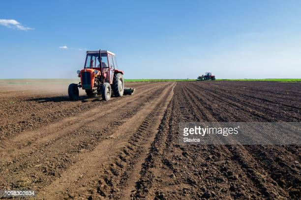 tractors sowing on agricultural field in spring - tractor stock pictures, royalty-free photos & images
