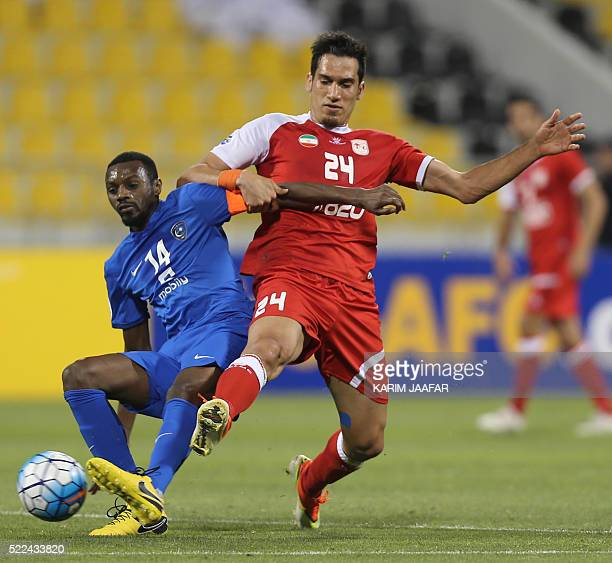 Tractorsazi Tabriz' Farzad Hatami vies for the ball with Al-Hilal's Saud Kariri during their AFC Champions League group stage football match in Doha...
