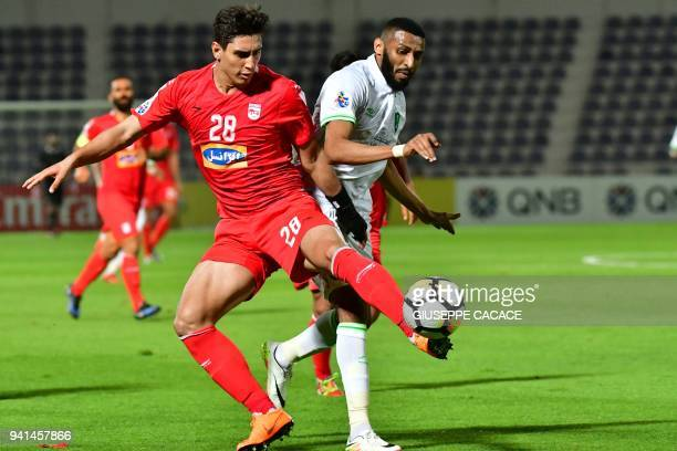 Tractorsazi Tabriz's defender Mohammad Naderi fights for the ball with Al Ahli's forward Muhannad Ahmed Abu Radiyah during the AFC Champions League...