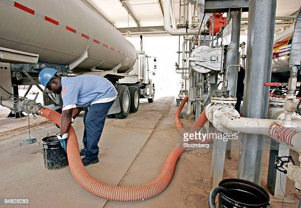 Tractor-trailer driver Quincy Miller prepares to disconnect a hose from his truck after delivering ethanol to a pumping station at the Motiva...