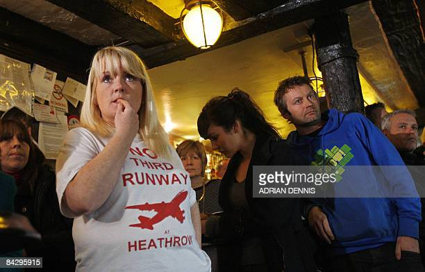 Tracy Howard a barmaid at The King William IV pub and local resident of Sipson close to Heathrow Airport watches the news on television as the...