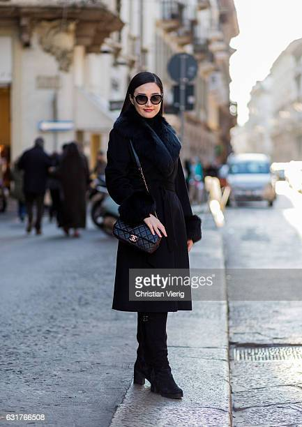 Tracy Liu is wearing a black coat Chanel bag black overknees during Milan Men's Fashion Week Fall/Winter 2017/18 on January 15 2017 in Milan Italy