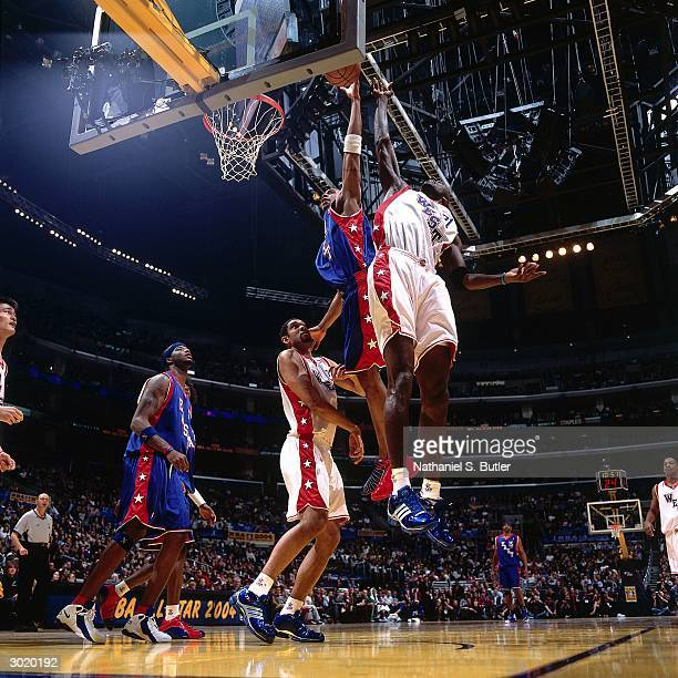 Tracy McGrady of the Eastern Conference AllStars dunks against Kevin Garnett and Tim Duncan of the Western Conference AllStars during the 2004...