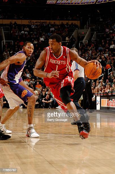 Tracy McGrady of the Houston Rockets drives around Shawn Marion of the Phoenix Suns on November 29 2006 at US Airways Center in Phoenix Arizona The...
