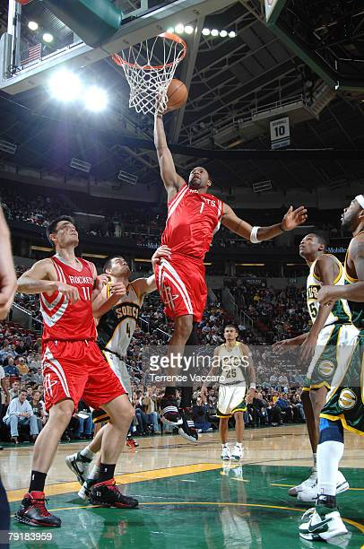 Tracy McGrady of the Houston Rockets goes to the basket between the defense of Nick Collison and Kevin Durant of the Seattle SuperSonics on January...