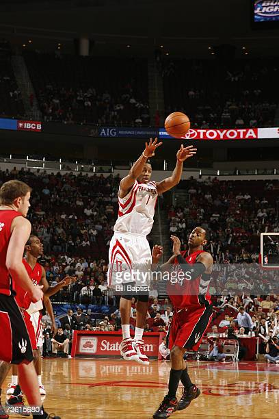 Tracy McGrady of the Houston Rockets makes a long pass away from Morris Peterson of the Toronto Raptors at the Toyota Center on February 28 2007 in...