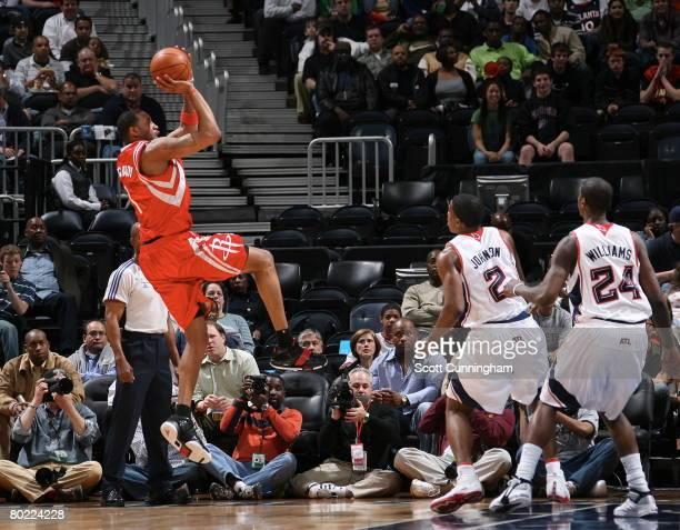 Tracy McGrady of the Houston Rockets shoots against Joe Johnson and Marvin Williams of the Atlanta Hawks at Philips Arena on March 12 2008 in Atlanta...
